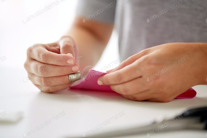 woman with needle stitching fabric pieces