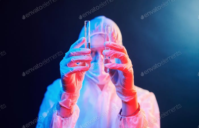 Nurse in mask and white uniform standing in neon lighted room and holding tubes with samples