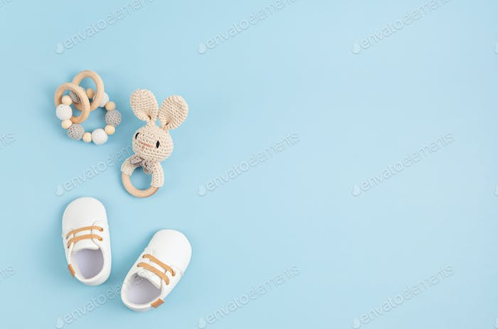 Gender neutral baby shoes and accessories over blue background