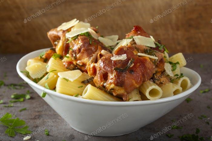 Chicken meat wrapped in prosciutto with tomato sauce and rigatoni pasta