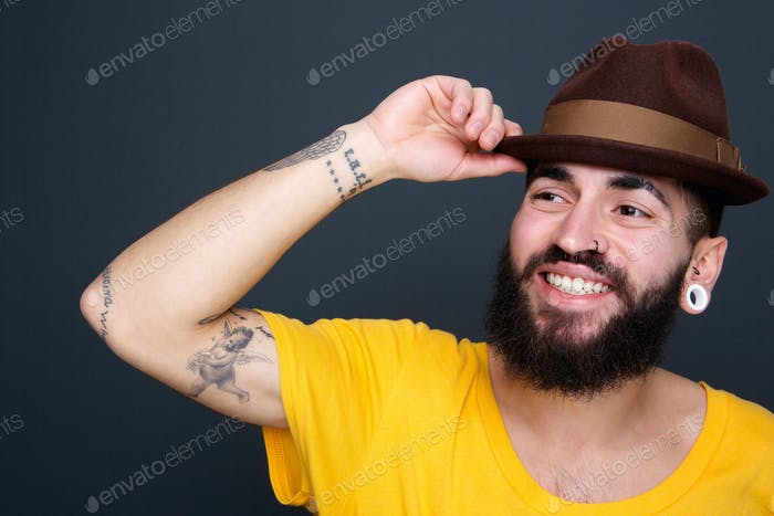 Man smiling with hat on gray background