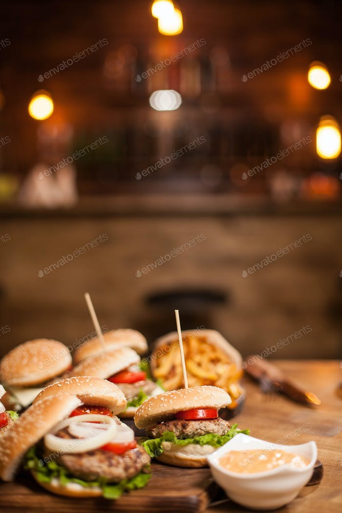 Close up of burgers with lettuce and counter bar blurred in the background