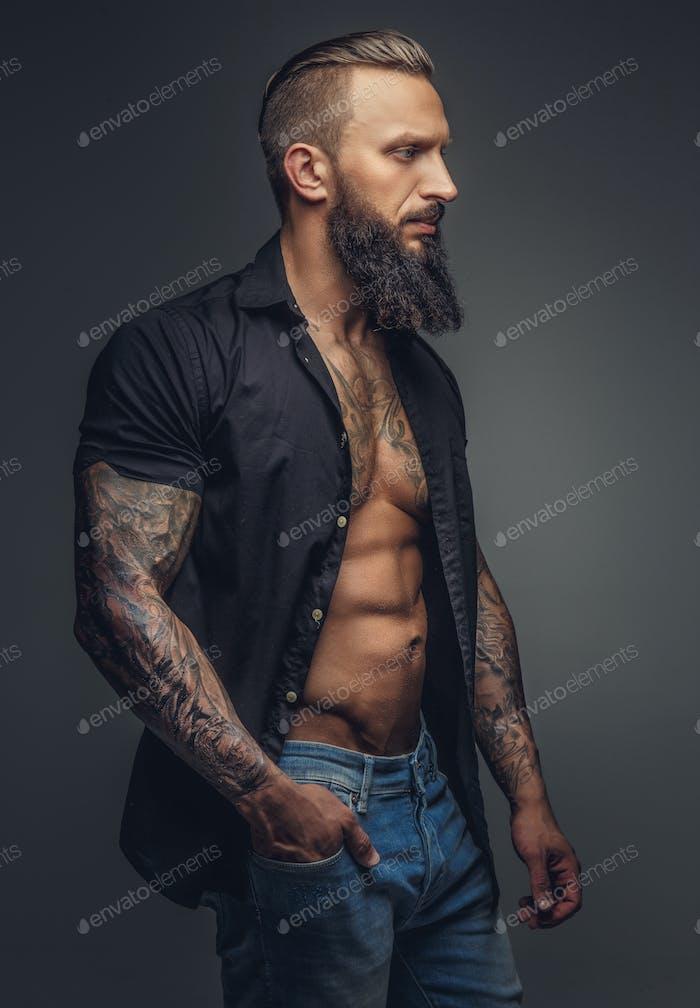 Fashionable tatooed man with beard.