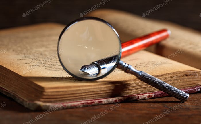 Ink pen and magnifying glass on an old book