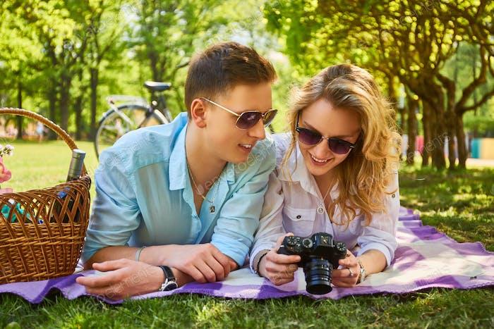 Paar mit einer kompakten Fotokamera bei einem Picknick.