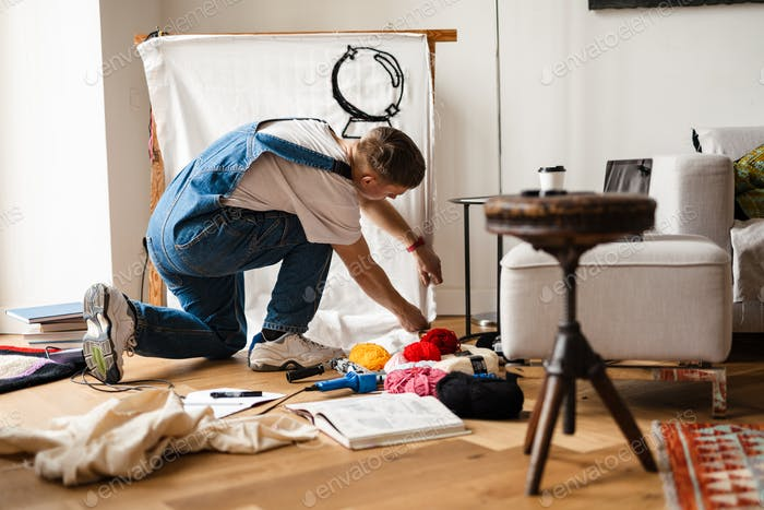 Young white man wearing overall working on craft rug at home