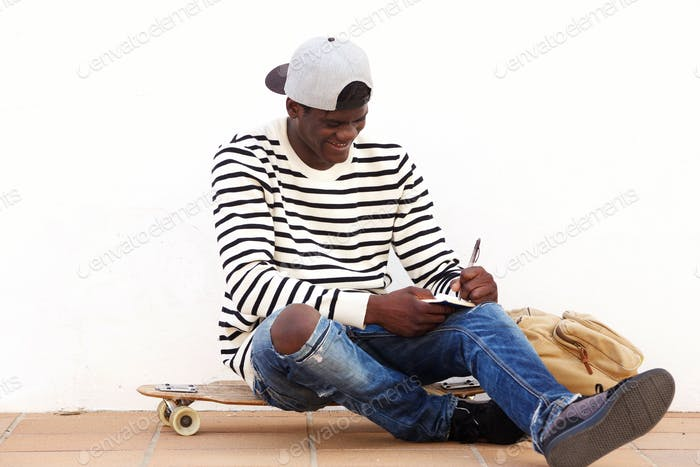 Cool young man sitting on skateboard outdoors and writing on book