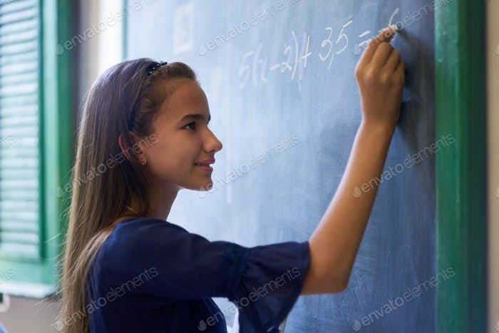 Girl Doing Math Exercise At Blackboard In High School Class