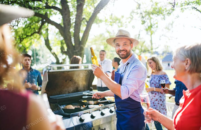 A mature man with family and friends cooking and serving food on a barbecue party.