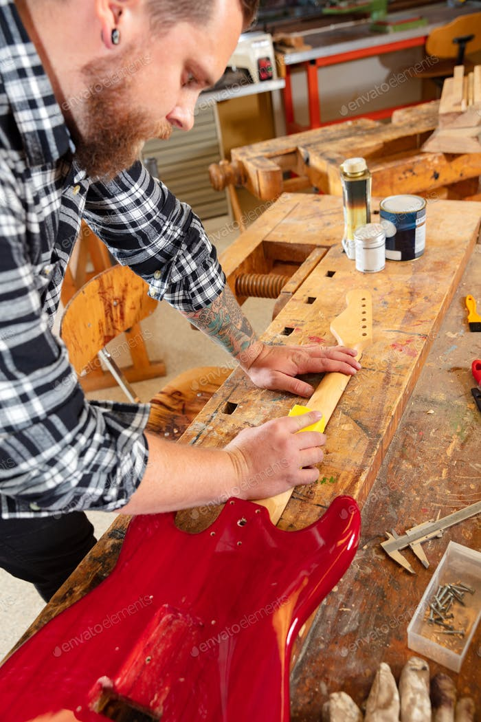 Close-up of a craftsman sanding a guitar neck in wood at workshop