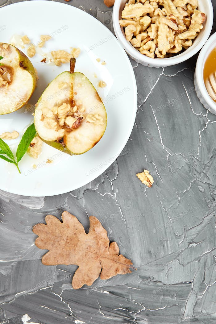 Tasty roast pears with honey and walnuts on grey background table.