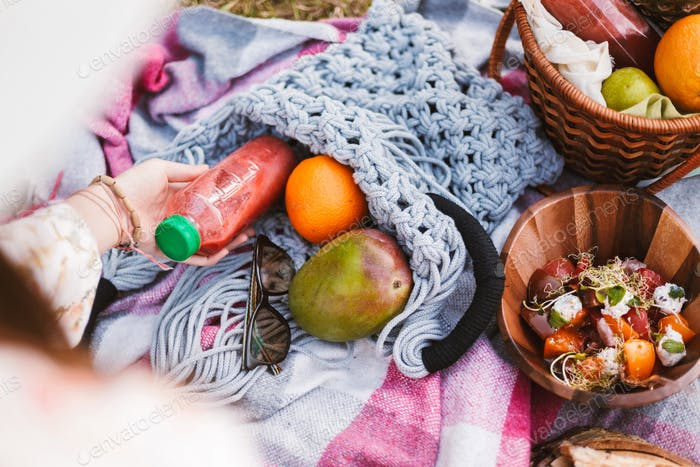 Close up photo of bag with juice bottle and fruits on picnic bla