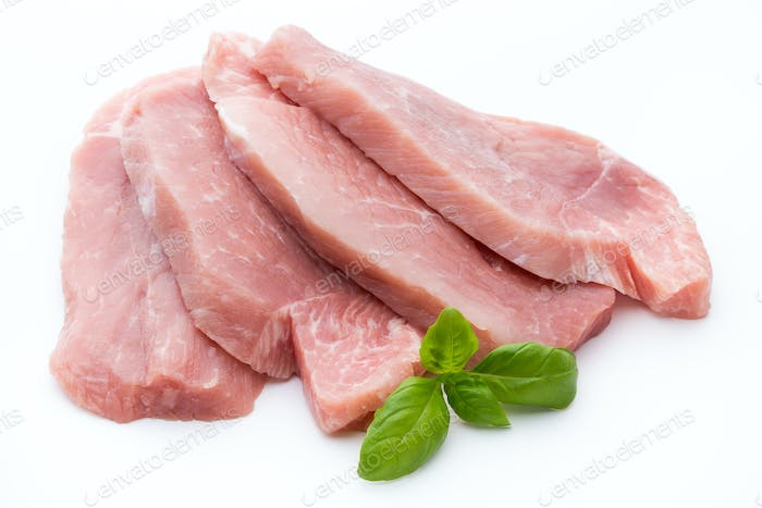 Fresh pork fillet with basil on a white background.