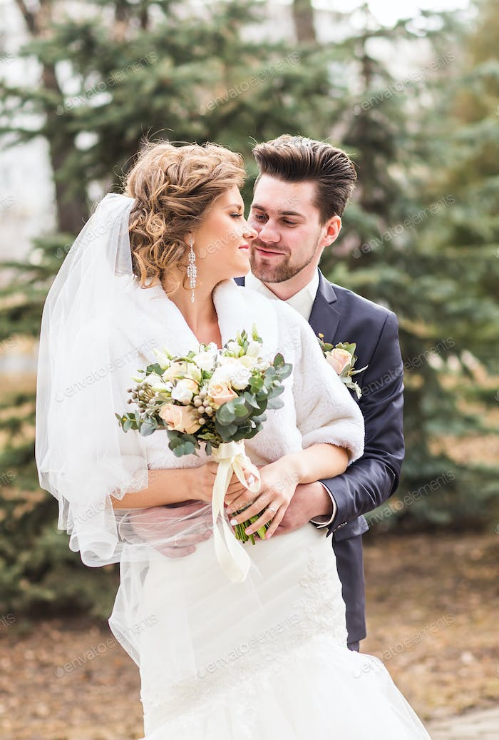 Newlyweds in autumn park, the groom embracing his bride.