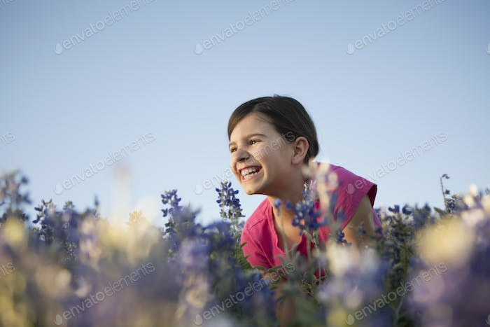 A girl sitting in a field of tall grass and blue wild flowers.