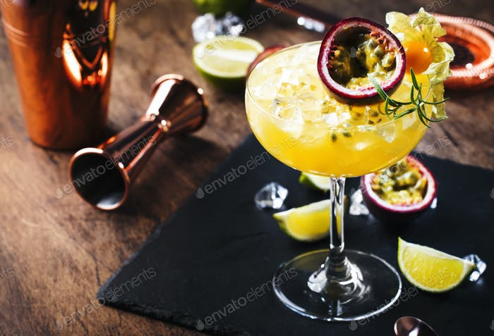 alcoholic cocktail with syrup, lime, orange juice, soda, ice and passion fruit