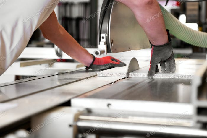 Carpenter cutting a wooden panel on a saw