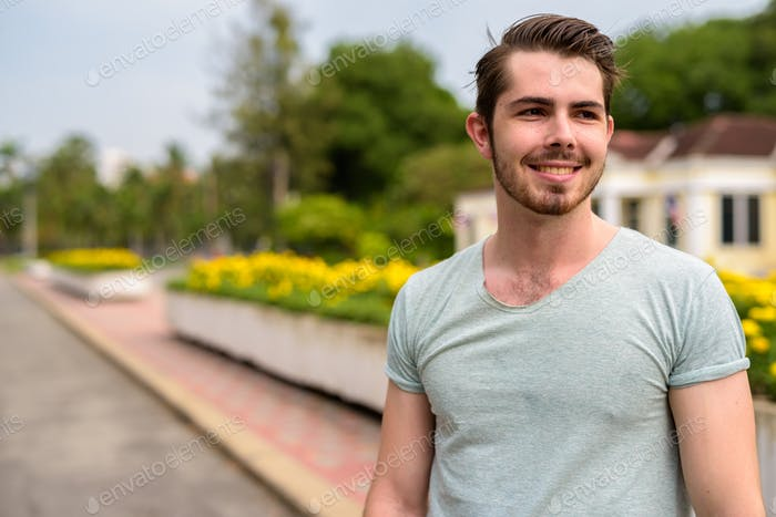 Portrait of young happy man relaxing at the park
