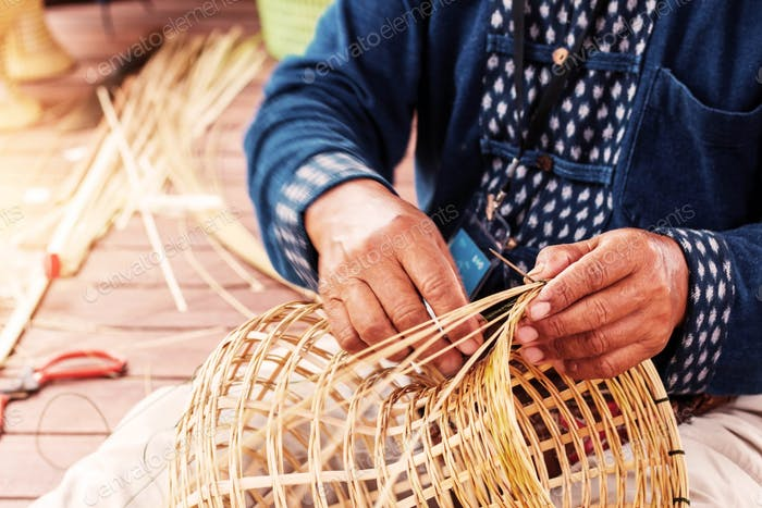 Hands weave bamboo baskets
