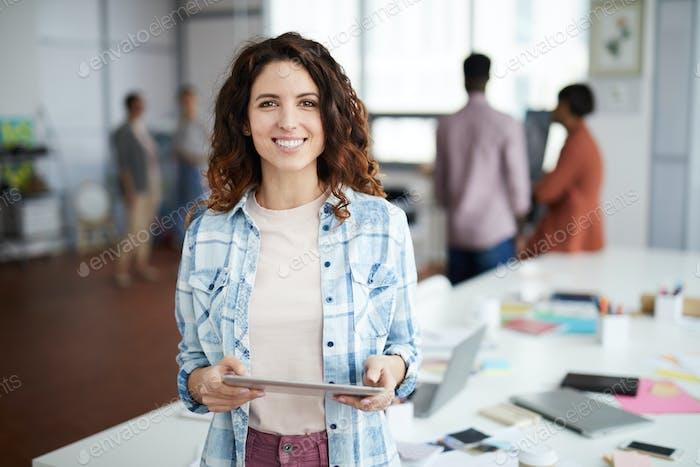 Веселая молодая женщина позирует в креативном Агентство