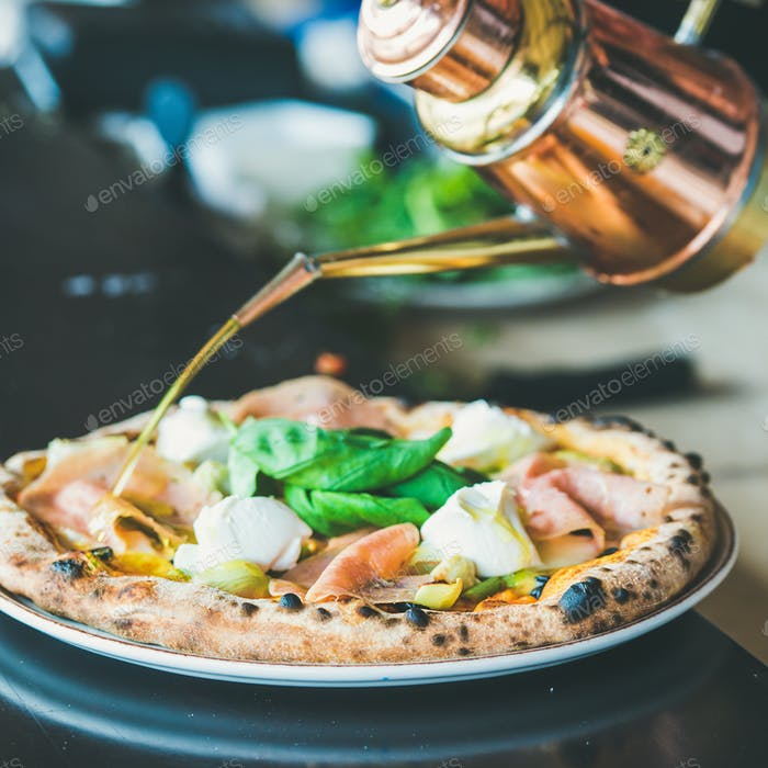 Freshly baked pizza with ham, artichokes and cheese, square crop