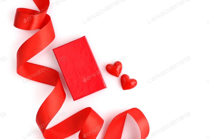 Valentines Day background. Red gift box and two glass heart on w
