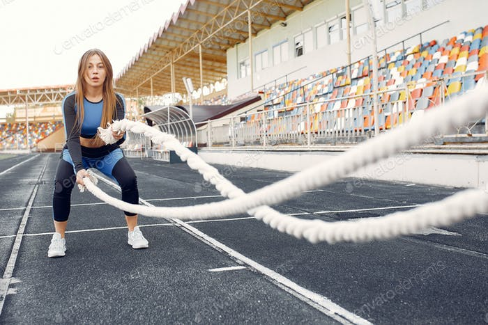 Sports girl in a blue uniform training at the stadium with rope