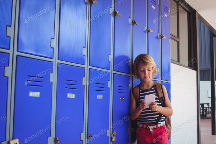 Schoolboy using mobile phone while standing by lockers