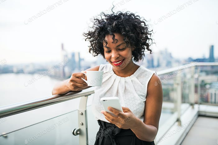 A businesswoman with coffee and smartphone standing against London view panorama.
