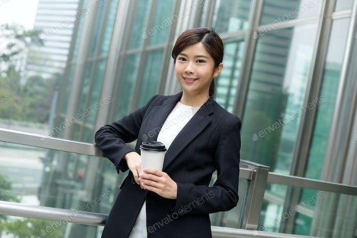 Geschäftsfrau hält mit Kaffeetasse