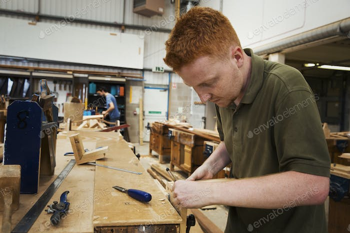 Man working a boat-builder's workshop, joining together two pieces of wood.