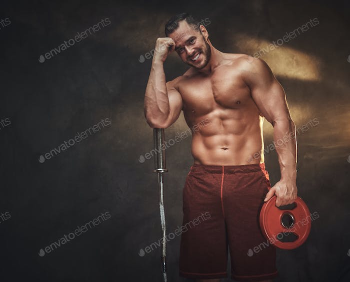 Young shirtless bodybuilder has a photo session
