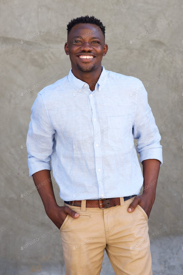 handsome african american man smiling by wall