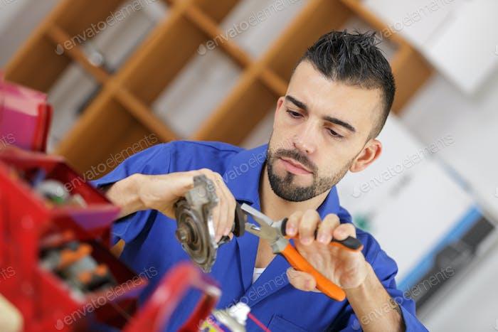 Workman using pliers of metal part