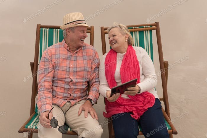 Happy senior couple using digital tablet while relaxing in a sun lounger at the beach