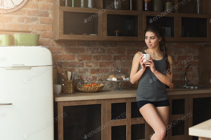 Happy young woman drinking morning coffee in kitchen