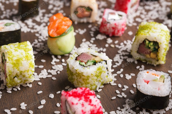Set of sushi, maki and rolls with sesame on wooden rustic background, closeup