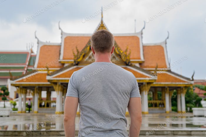 Rear view of young tourist man against view of the Buddhist temple in Bangkok
