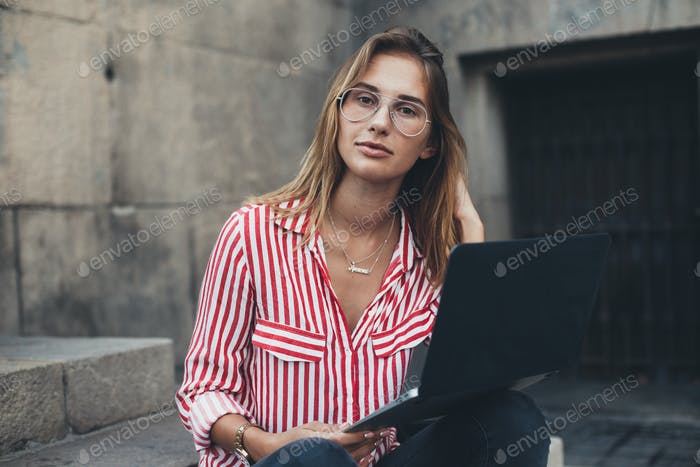 Woman with laptop sitting on stairs at university