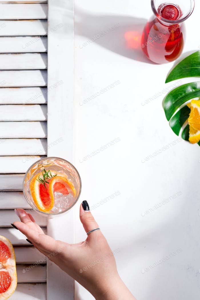 Woman's hand takes cold summer drink in a glass with slice of grapefruit above a white