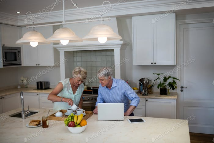 Senior couple using laptop while having tea in kitchen
