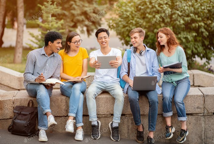 Multiracial students studying together in the park