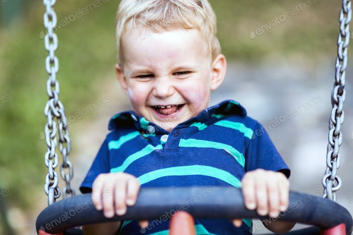 Playful child on swing outdoors