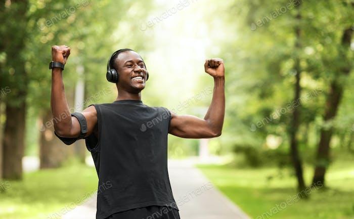 Черный спортсмен празднует успех, тренируясь в парке