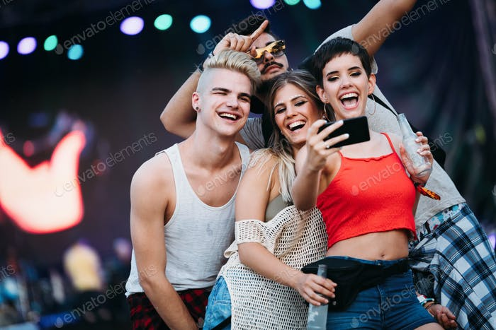Happy friends taking selfie at music festival