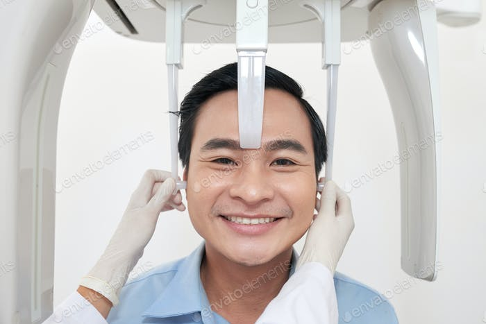 Smiling patient during usage of dental x-ray machine
