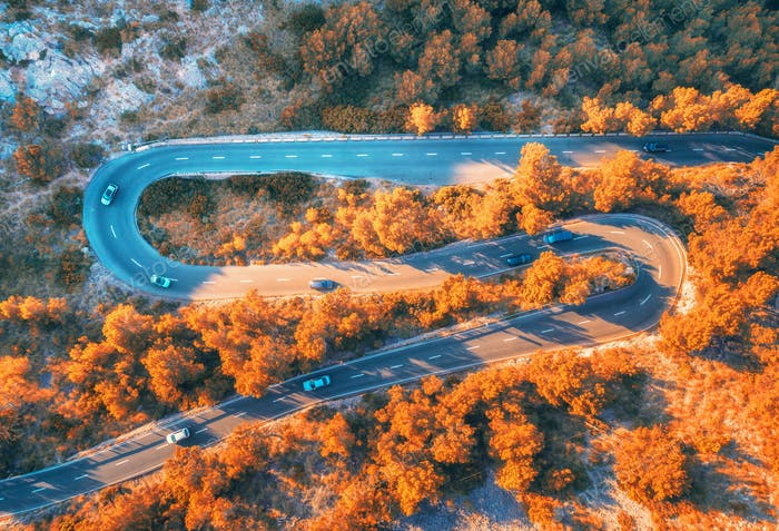 Aerial view of winding road in autumn forest at sunset