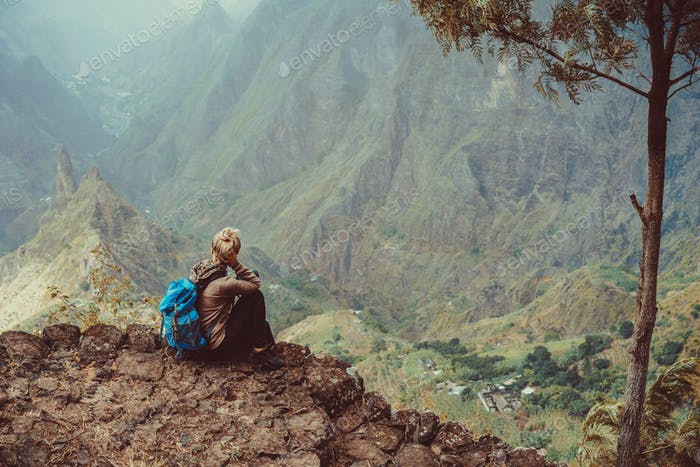 Female sitting in front of breathtaking panorama of deep lush ribeira surrounded by towering peaks