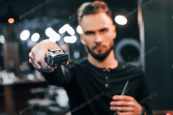Young bearded man standing in barber shop and holding clipper