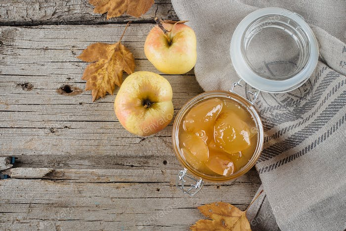 Homemade apple jam or sauce in jar on table. Wooden rustic background copy space, top view